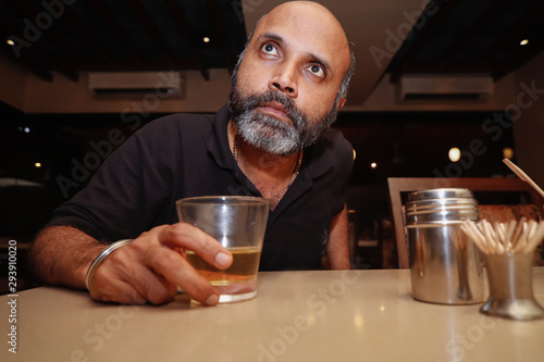 A model posing as a drunk man looking into his glass of drink Tablou Canvas