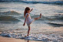 Little Girl Running Through The Water With A Splash . In Her Hands Cloth
