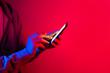 Leinwanddruck Bild - Male hand with smartphone. Finger typing on screen. Neon light