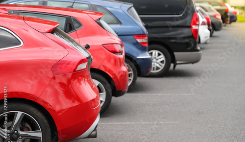 Fotomural  Closeup of rear, back side of red car with  other cars parking in outdoor parking area