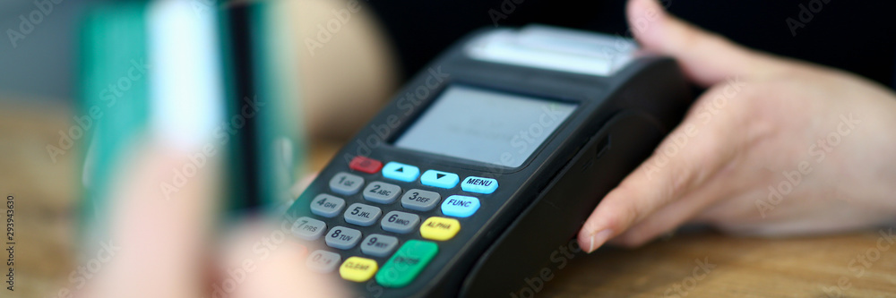 Fototapeta Customer paying with credit card via payment terminal at cash desk background concept