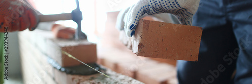 Photo Male builder hand in gloves holding clay brick on background of brickwork wall
