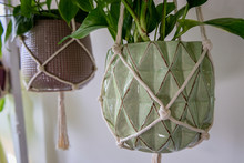 A Beautifully Textured Green And Brown Coloured Plant Pot Is Hanging From A Cotton Macrame. A Second Pot Is Hanging In The Background.