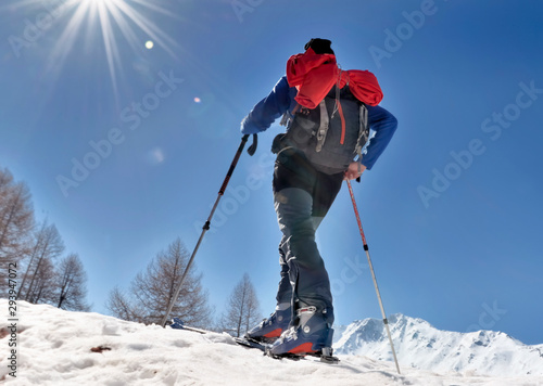 touring skier climbing mountain under sunny blue sky