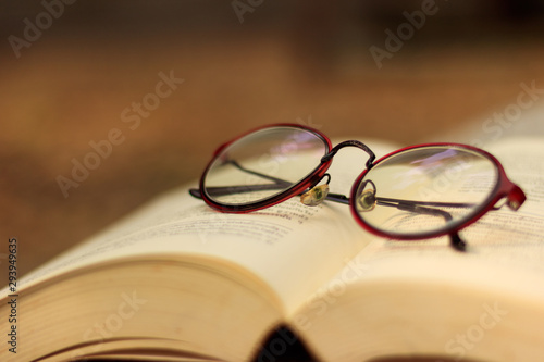 Fotografía  Brown glasses Put on the book. Brown tone background, copy space
