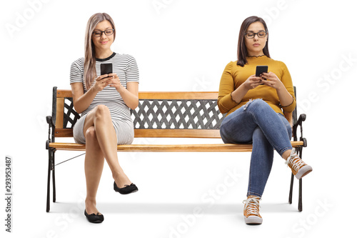 Cuadros en Lienzo Two young women sitting on a bench and typing on smartphones