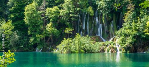 Obraz Crystal clear, pure water rushing down mossy rocks into a beautiful azure colored lake at the Plitvice Lakes National Park, Plitvička Jezera, Croatia - fototapety do salonu