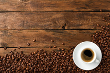Coffee Cup With Beans On Vintage Wooden Table With Copyspace. Top View