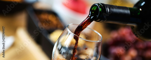 Red wine pouring into a wine glass at a tasting with various types of appetizers Fototapeta