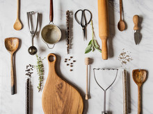 Flat Lay Various Metal, Wooden Kitchen Tools And Dry Spices In Glass Tube And Raw Herbs On A Marble Background. Top View.
