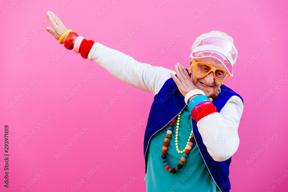 Fototapeta Funny grandmother portraits. 80s style outfit. Dab dance on colored backgrounds. Concept about seniority and old people