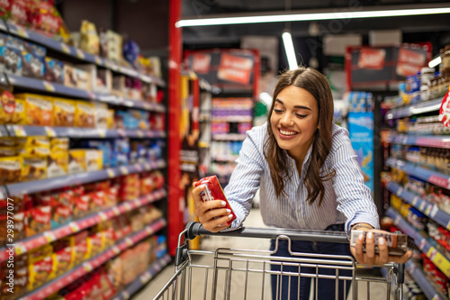 Woman with shopping trolley in supermarket aisle. Buying food in grocery store. Grocery shopping. Beautiful young woman shopping in a grocery store/supermarket