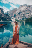 Girl in a straw hat on the background of the turquoise lake with wooden boats in mountains. Safari style blonde woman. Dolomites Alps, lago di Braies, Italy