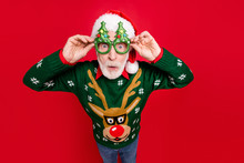 Photo Of Funny Grey Haired Santa Looking On Unbelievable Low X-mas Shopping Prices Speechless Wear X-mas Tree Shape Specs Ugly Ornament Sweater Isolated Red Background