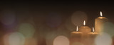 Christmas advent candle light in church with blurry golden bokeh for religious ritual or spiritual zen meditation, peaceful mind and soul, or funeral ceremony