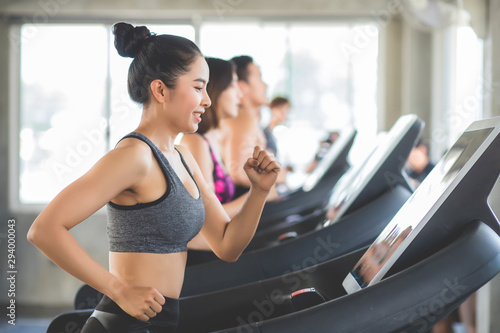 Beautiful Asian women Thai people have tan skin, long hair and tied hair in a sports bra doing exercise by running on the electric treadmill in the fitness room in Thailand Fototapet