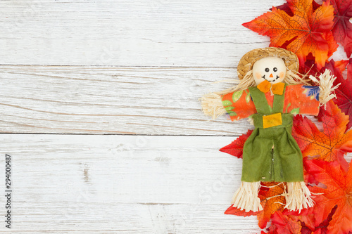 Fotografia Red and orange fall leaves with a scarecrow on weathered whitewash wood textured