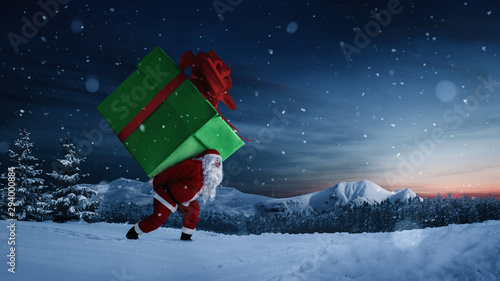 Santa Claus carrying huge christmas gift at night with copy space Canvas Print