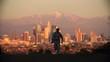 Man runs away, cityscape from LA at sunset, California, USA.