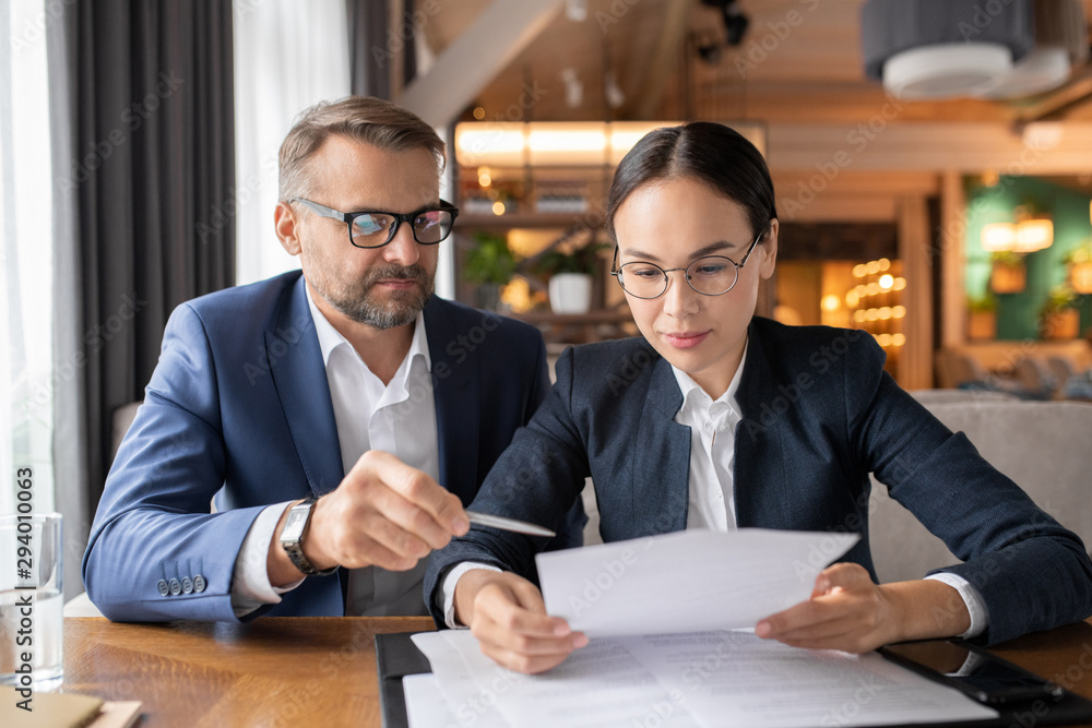 Fototapeta Confident businessman pointing at contract while his female colleague reading it