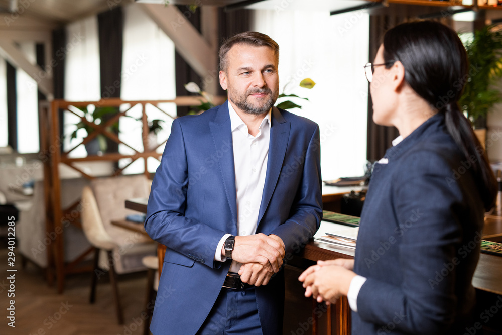 Fototapeta Two contemporary owners of modern restaurant having discussion of working points