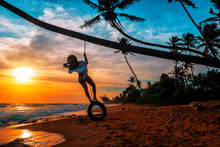 Girl Stands On A Wheel Tied To A Palm Tree