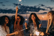 canvas print picture Four happy women celebrating at sunset with sparklers