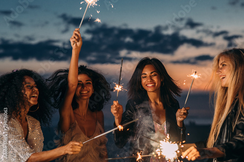 Obraz Four happy women celebrating at sunset with sparklers - fototapety do salonu