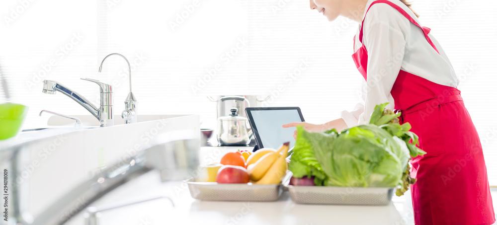 Fototapeta キッチンでタブレットを使う女性