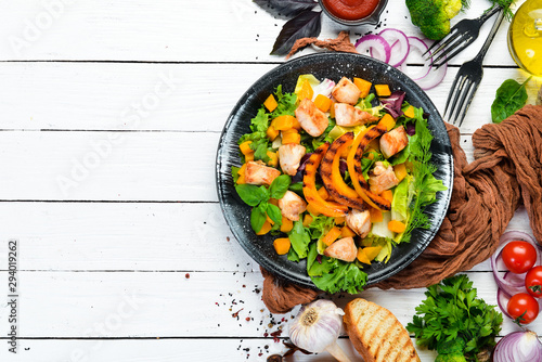 Pumpkin salad with chicken meat and vegetables in a black plate on a white wooden background. Top view. Free space for your text.