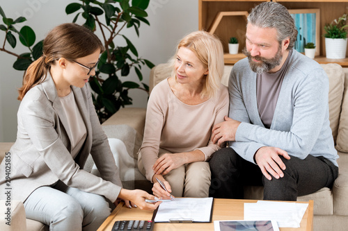 Fotografía  Mature blonde woman listening to real estate agent while going to sign contract