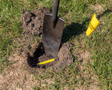 Buried Plastic Natural Gas Line In Hole Of Yard. Shovel In Soil And Yellow Buried Gas Warning Flag Marking Location. Concept Of Notify Utility Location Company For Underground Utitilies Before Digging