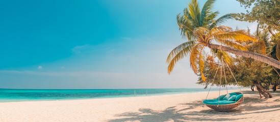 Panorama tropikalnej plaży jako letni krajobraz z huśtawką lub hamakiem i białym piaskiem i spokojnym morzem na baner plażowy. Idealna koncepcja na wakacje i wakacje na plaży. Popraw proces koloru