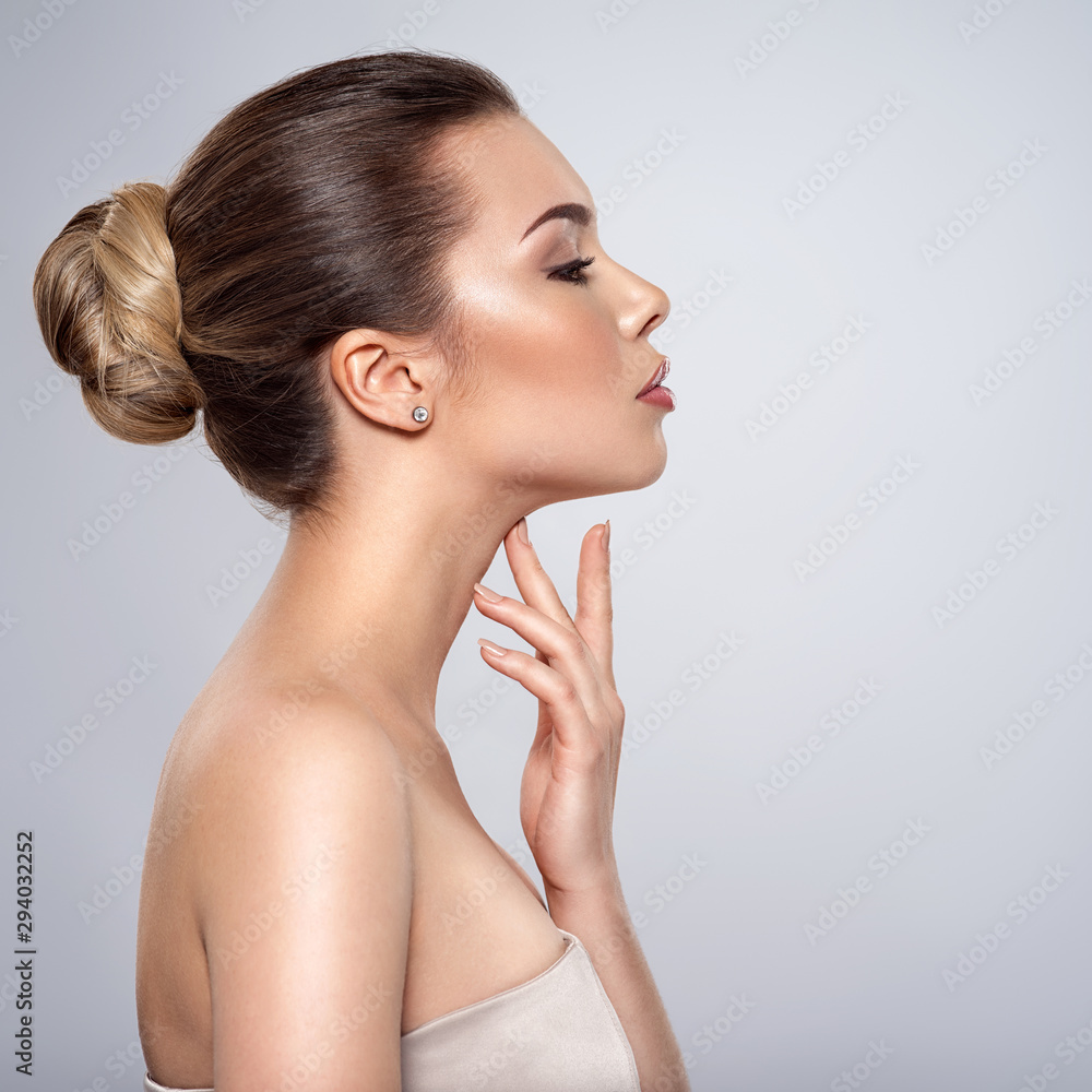 Fototapeta beautiful woman who touches the neck by fingers