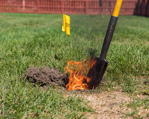Real black smoke and flames rise from fire in hole of yard. Natural gas warning flag and shovel. Concept of notify utility locating company for underground utilities before digging and safety Wall mural