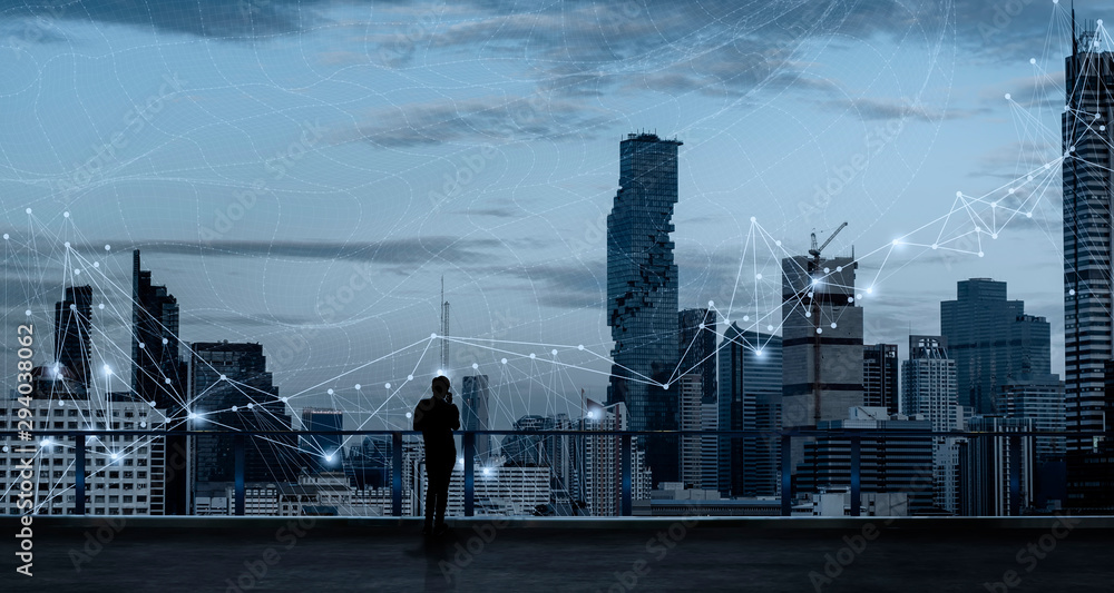Fototapeta Businessman standing using smart phone in modern space watching city night view.Business Wireless network and Connection technology concept.