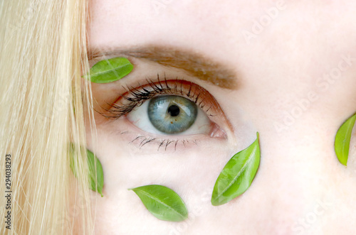 Poster Spa Eyes of a girl with green leaves. Moisturizing, beauty and skin care. The concept of natural and organic cosmetics