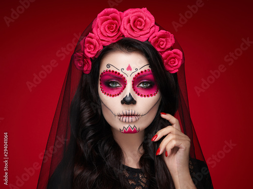 Portrait of a woman with sugar skull makeup over red background Fototapet