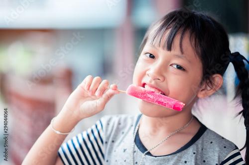 Pinturas sobre lienzo  Beautiful asian little girl eats ice-cream in the summer at home