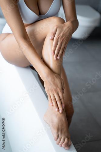 Fototapeta Caucasian woman applying a moisturizing body cream obraz na płótnie