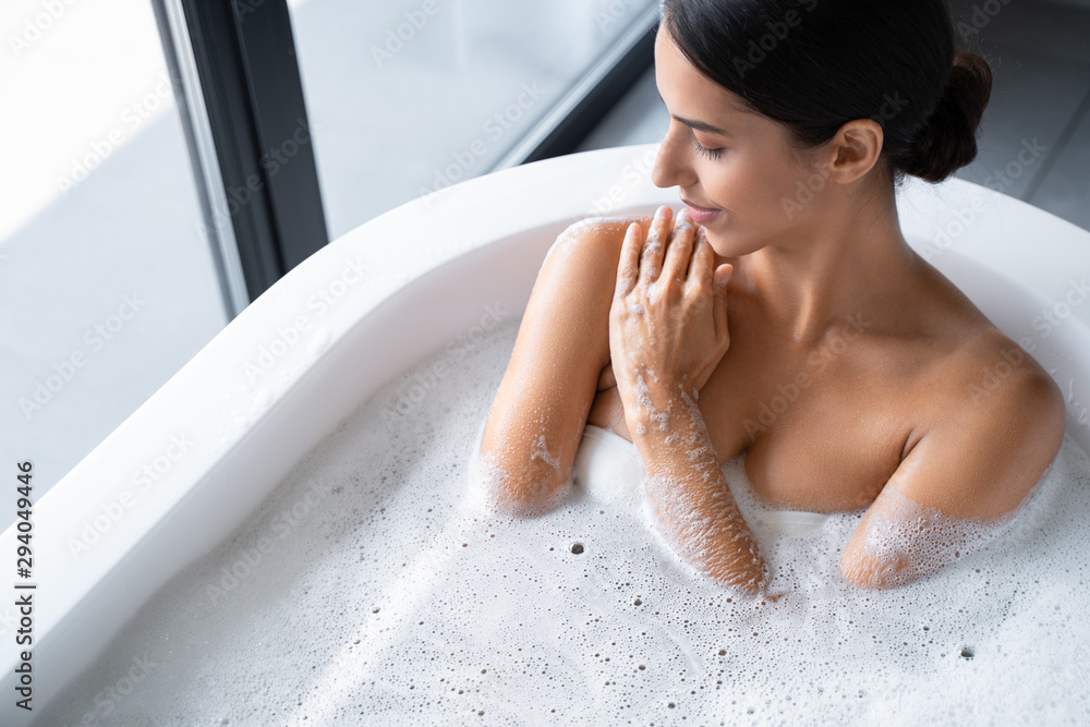 Fototapeta Relaxed young lady is having a bath