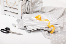 Process Of Sewing Of Bed Linen. Sewing Kit. Grey Fabric, Scissors, Threads, Measuring Tape And White Old Wooden Box On White Wooden Background