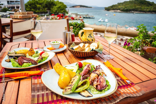 Fotografie, Obraz  Grilled seafood stuffed with vegetables and lemon on the table in seafront