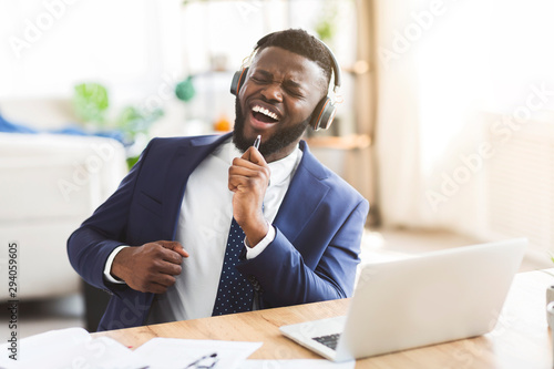 Handsome businessman singing and listening to music with headphones - 294059605