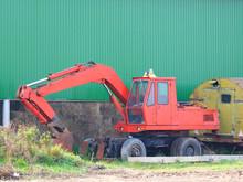 Excavator In The Parking Lot Opposite The Hangar