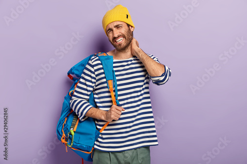 Fototapeta Fatigue tourist touches neck, feels stiffness, dressed in casual clothes, carries rucksack, has painful feelings, looks unhappily at camera, poses over purple background. People and tiredsome journey obraz