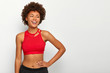 Half length shot of cheerful fitness woman keeps hand on waist, being in good physical shape, wears red top, turns gaze away with happy smile, enjoys spending free time in gym, motivates you to sport