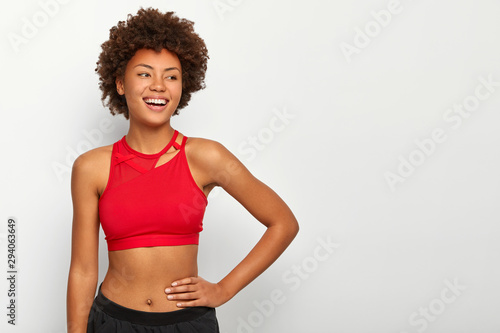 Tablou Canvas Half length shot of cheerful fitness woman keeps hand on waist, being in good ph