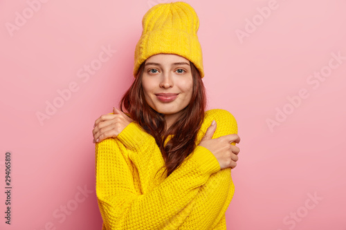 Tablou Canvas Horizontal shot of attractive young woman hugs herself, has dark long hair, tender look, wears yellow winter hat and sweater, poses against pink studio background