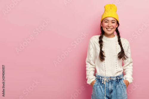Photo Studio shot of happy Asian woman with tender smile, keeps both hands in pockets